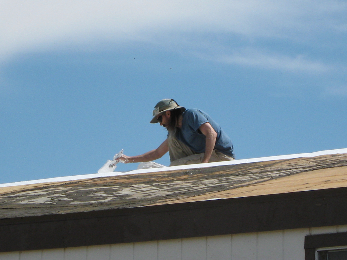 Embedding poly-mesh in first coat of elastomeric coating on mobile home roof
